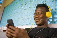 Livsstilstående av den unga svarta afro amerikanska mannen för attraktiv och lycklig kall hipster som använder på mobiltelefon- o arkivbild
