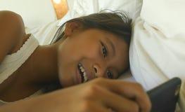 Livsstilstående av det söta kvinnliga barnet, en lycklig och härlig ung flicka som har den roliga spela internetleken med mobilte arkivbilder
