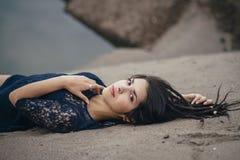 Livsstilstående av en kvinnabrunett på bakgrund av sjön som ligger i sand på en molnig dag Romantiker försiktigt som är mystisk royaltyfri foto