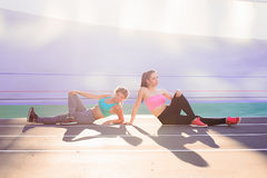 Livsstilstående av två barn och idrotts- flickor som gör uppvärmning och genomkörare och sträckning royaltyfri foto
