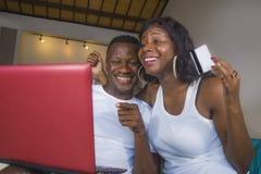 Livsstilstående av unga lyckliga och attraktiva svarta afro amerikanska par som hemma tycker om använda kreditkort- och bärbar da royaltyfri fotografi
