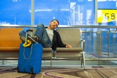 Livsstilstående i flygplats av den unga attraktiva och trötta turist- mannen med resväskan som sover på den väntande på annulleri fotografering för bildbyråer