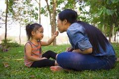 Livsstilst?endemamma och dotter i lycka p? yttersidan i ?ngen, rolig asiatisk familj i en risf?lt fotografering för bildbyråer