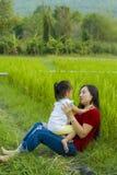 Livsstilst?endemamma och dotter i lycka p? yttersidan i ?ngen, rolig asiatisk familj i en risf?lt arkivbild