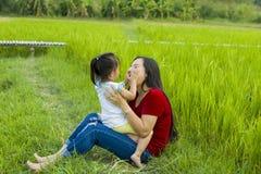 Livsstilst?endemamma och dotter i lycka p? yttersidan i ?ngen, rolig asiatisk familj i en risf?lt arkivfoto