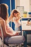 Livsstiltillfångatagandet av den gravida modern och behandla som ett barn flickan som har frukosten hemma Royaltyfri Fotografi