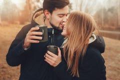Livsstiltillfångatagandet av lyckliga par som dricker varmt te som är utomhus- på hemtrevligt varmt, går i skog fotografering för bildbyråer