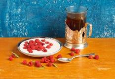 1 livstid fortfarande Hallon med gräddfil och ett exponeringsglas av te Arkivbild
