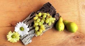 1 livstid fortfarande Mat Druvor, päron och blommor på lantlig träbakgrund, överkant Royaltyfria Bilder