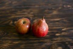 1 livstid fortfarande Päron och äpple på en brun bakgrund, på en skärbräda arkivbilder