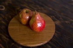1 livstid fortfarande Päron och äpple på en brun bakgrund, på en skärbräda arkivfoto