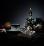 1 livstid fortfarande stearinljus i bronsljusstaken, kopp, orange bukett av rosor, klocka natt Royaltyfri Foto