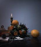 1 livstid fortfarande stearinljus i bronsljusstaken, orange bukett av rosor, klocka natt Arkivbild