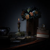 1 livstid fortfarande stearinljus i bronsljusstaken, orange bukett av rosor, klocka natt Royaltyfria Bilder