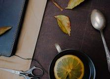1 livstid fortfarande Tappning anteckningsbok citronte, en silversked på papper Närbild Arkivfoton