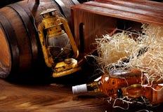 1 livstid fortfarande Whiskyflaskor Gammalmodig lampa för olja, träbehållare med trächiper och trätrummor royaltyfri bild