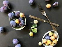 śliwki i mirabelki na ceramiczni talerze na czarnym tle fotografia royalty free