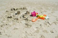 Lixe castelos e caçoe brinquedos na praia Fotografia de Stock Royalty Free