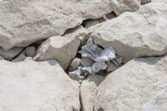 Lixo da folha de alumínio colado entre rochas fotografia de stock