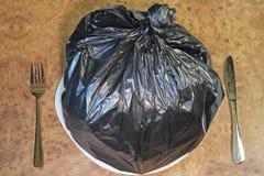 Lixo do alimento com forquilha e faca Fotos de Stock Royalty Free