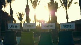 Lixo, lixo, escaninhos rubish para o v?rio lixo, com sinais para classificar o vidro, o papel, o pl?stico e o metal no por do sol filme