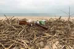 Lixo na praia Garrafas plásticas vazias e juncos secos na areia Poluição ambiental fotos de stock