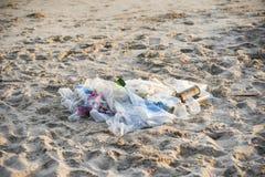 Lixo no mar com a garrafa plástica do saco e no outro mar sujo arenoso da praia do lixo na ilha foto de stock