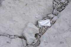 Lixo vazio do malote do suco que coloca em rochas imagens de stock