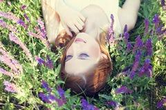 Liyng de la muchacha en hierba de la primavera    Foto de archivo
