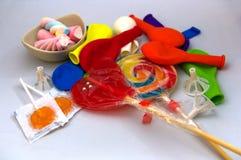Lizaki, jellybeans i balony na białym stole, zdjęcie stock