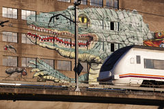 Lizard graffiti on a building facade and train Stock Photography