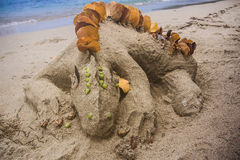Lizard Sand Castle. A lizard sculpted out of sand with various details made from beach vegetation royalty free stock images