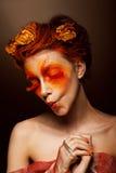 Grimas. Humoristisk rolig kvinna med blommor som har gyckel. Scenisken utformar Arkivbilder