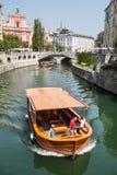 Ljubljana, Eslovenia Río de Ljubljanica Edificio blanco y barco turístico Fotos de archivo libres de regalías
