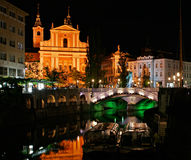 Ljubljana at night. The heart of Ljubljana at night, including the Triple Bridge and the Franciscan Church, the river and two boats Royalty Free Stock Image