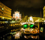 Ljubljana at night: bridge, church, boats Royalty Free Stock Images