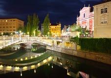 Ljubljana på natten, med den trefaldiga bro- och Franciscankyrkan Arkivfoton