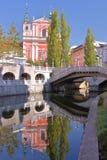 LJUBLJANA, SLOVENIË: Bezinningen van de Kerk van de Aankondiging en de Drievoudige Brug in de rivier Ljubljanica Royalty-vrije Stock Foto