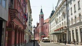 Ljubljana, Slovenië - 07/17/2015 - Weergeven van Franciscan Kerk en oude stadsstraat, zonnige dag royalty-vrije stock foto's