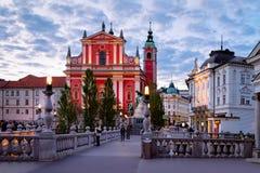 Ljubljana Slovenien - April 27, 2018: Folk på den Franciscan kyrkan av förklaringen och den trefaldiga bron i den historiska mitt arkivfoto