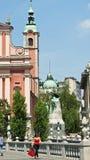 Ljubljana, Slovenien - 07/19/2015 - trefaldiga broar för bro 3 över Ljubljanica och del av den Franciscan kyrkan i centret, arkivfoto