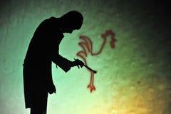 Ljubljana, Slowenien (Europa) 21. November 2012 Schattentheater: Mann, der einen Hahn zeichnet Lizenzfreie Stockfotos