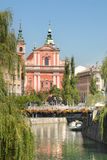 Ljubljana with wooden bridge tromostovje and a church behind Stock Photos