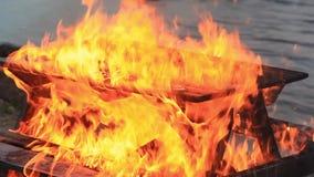 ljud Närbildvideo av en brinnande picknicktabell med ökande styrka vid en kropp av vatten