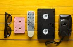 Ljudkassett vhs, 3d exponeringsglas, tvfjärrkontroll, hipsterfilmkamera på en gul träbakgrund Retro apparater från 80-tal Top bes Arkivbild