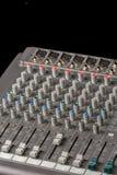 Ljudsignal blandande konsol med knoppar och glidare och svart bakgrund Arkivfoto