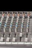 Ljudsignal blandande konsol med knoppar och glidare och svart bakgrund Fotografering för Bildbyråer