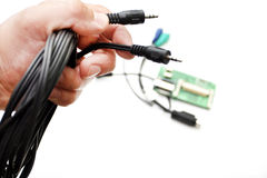 Ljudsignal en kabel i en hand på en vit bakgrund Royaltyfri Bild