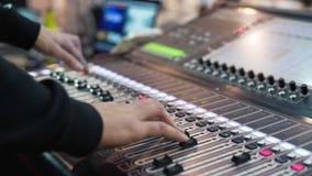 Ljudsignal tekniker som arbetar på en yrkesmässig konsol, rörande faders, blandande musik arkivfilmer