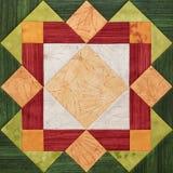 Ljus apelsin-gräsplan geometriskt patchworkkvarter från stycken av tyger, detalj av täcket arkivfoton